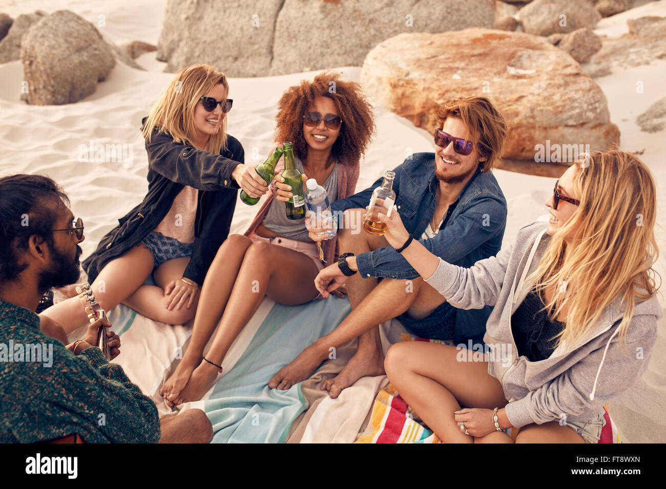 Group of young people toasting beers while sitting at the beach. Mixed race friends celebrating with drinks at beach - Stock Image