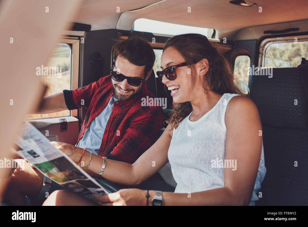 Happy young couple planning their travels together reading a map while sitting in their car. Smiling man and woman - Stock Image