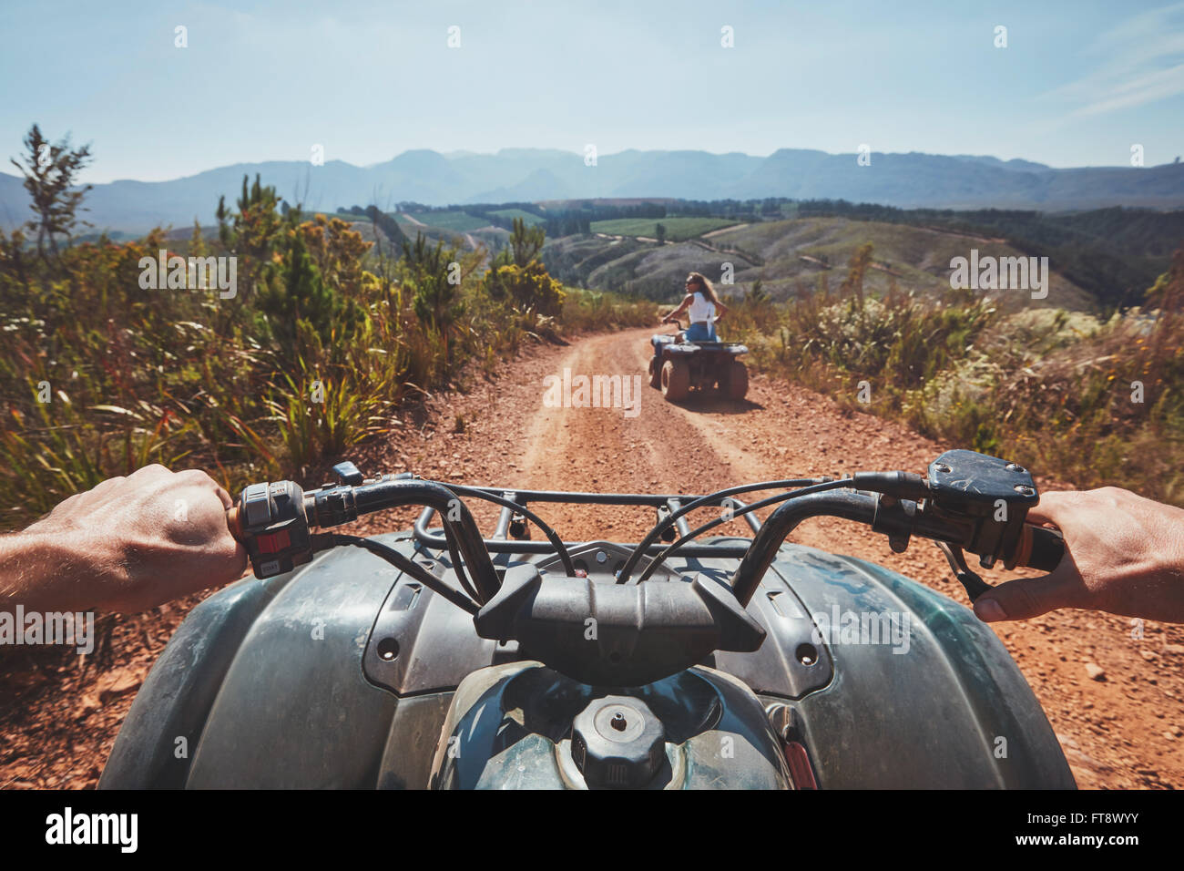 View from a quad bike in nature. Woman in front driving off road on an all terrain vehicle. POV image of a quad - Stock Image