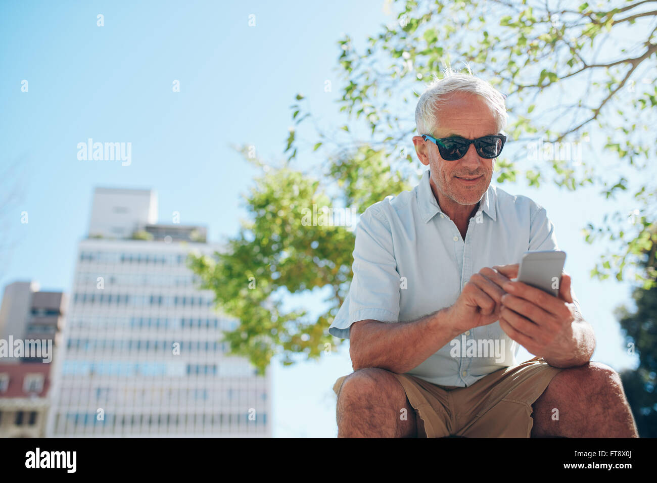 Low angle view of mature man sitting outdoors using mobile phone. Mature tourist resting outside in the city and - Stock Image