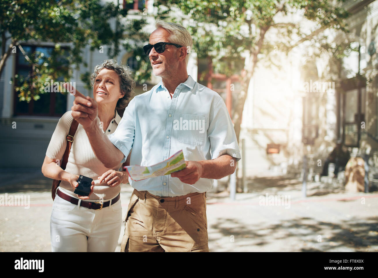 Mature couple tourist exploring a foreign city. Senior couple using map and looking for the direction. - Stock Image