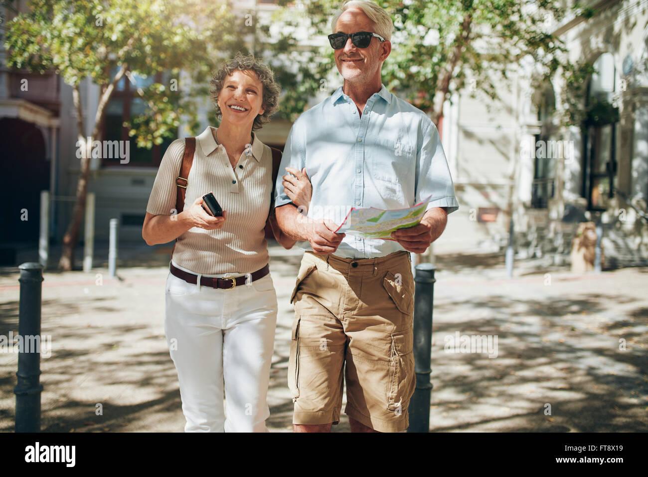 Senior couple walking around the city holding a map. Mature couple with a map roaming around the city. - Stock Image