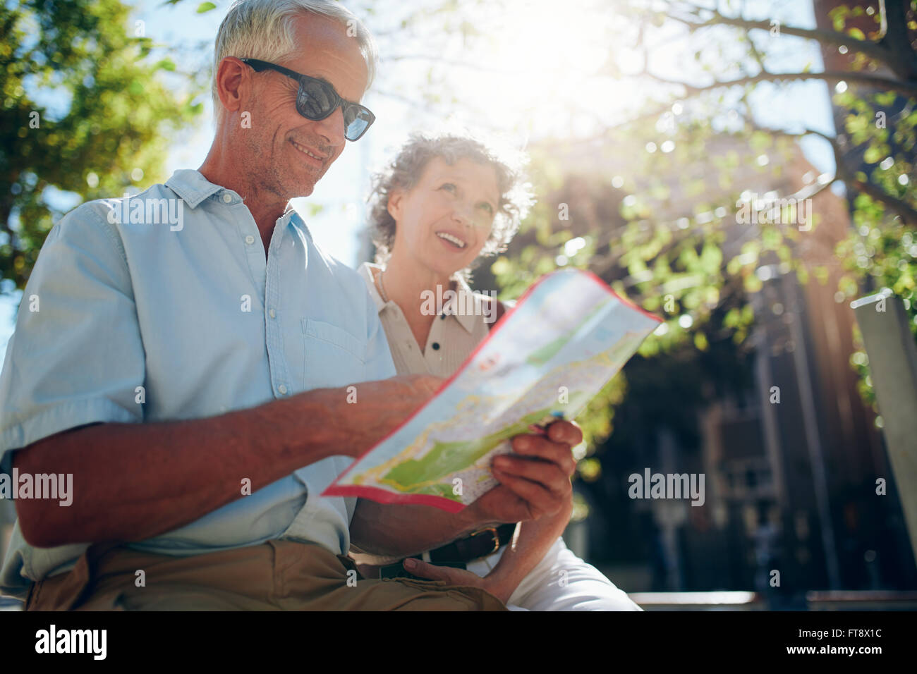 Senior couple together in the city looking at at map for directions. Mature man and women using city man on sunny - Stock Image