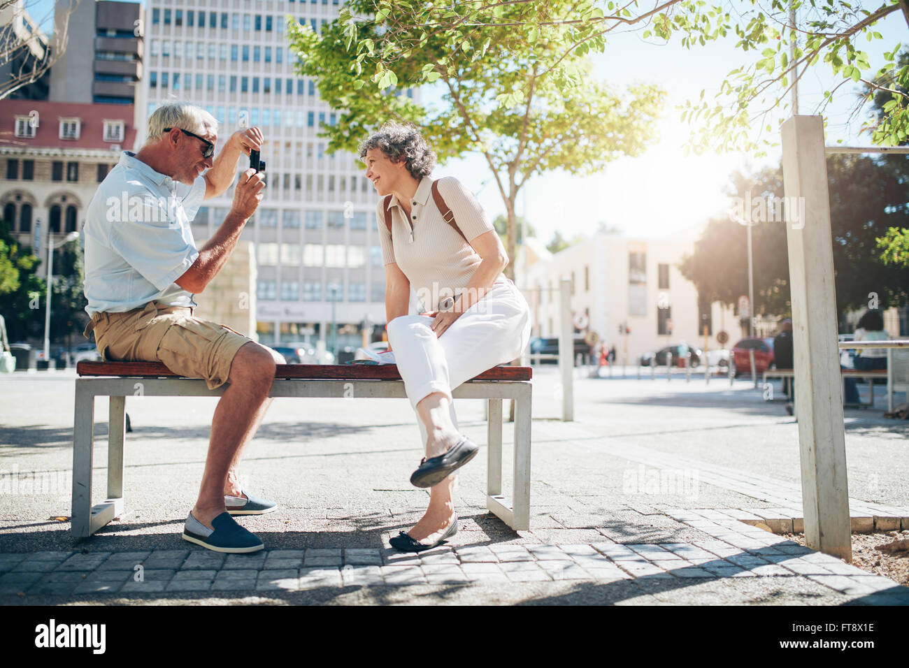 Side view of senior couple taking pictures while on vacation. Mature couple sitting outdoors on a bench photographing - Stock Image