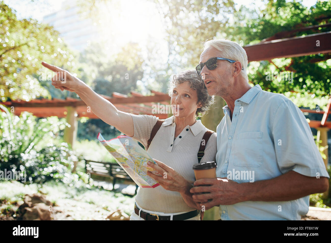 Couple of senior tourists using a city guide searching locations and pointing - Stock Image