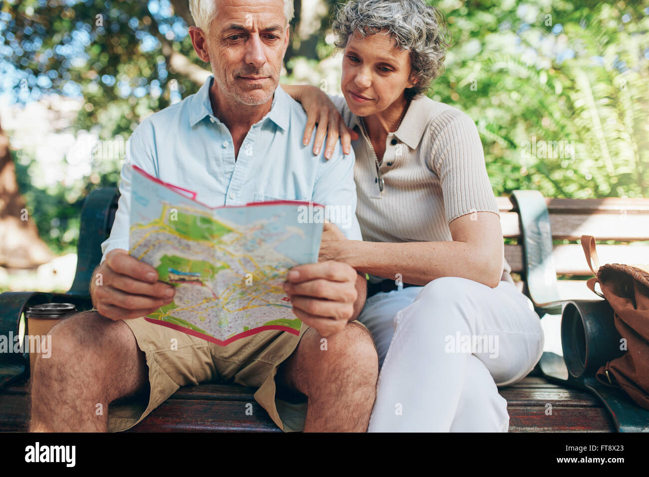 Senior tourist sitting on a park bench reading city map. Man and woman using city guide for finding their location. - Stock Image