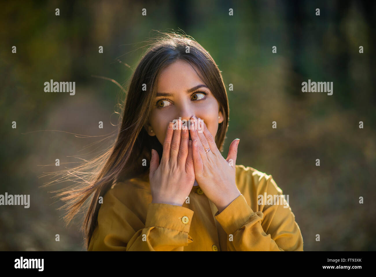 Amazed girl. Nice teenager girl having surprised expression on her face and covering her mouth with hands. Action - Stock Image