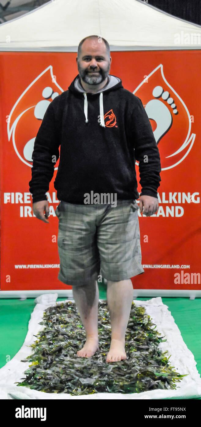Lisburn, Northern Ireland. 25 Mar 2016 - A man walks barefoot on broken glass - Stock Image