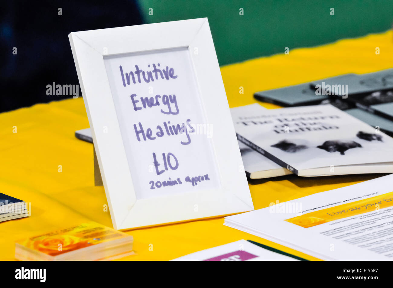 A sign advertises Intuitive Energy Healings for £10 at a holistic and spiritual fair. - Stock Image