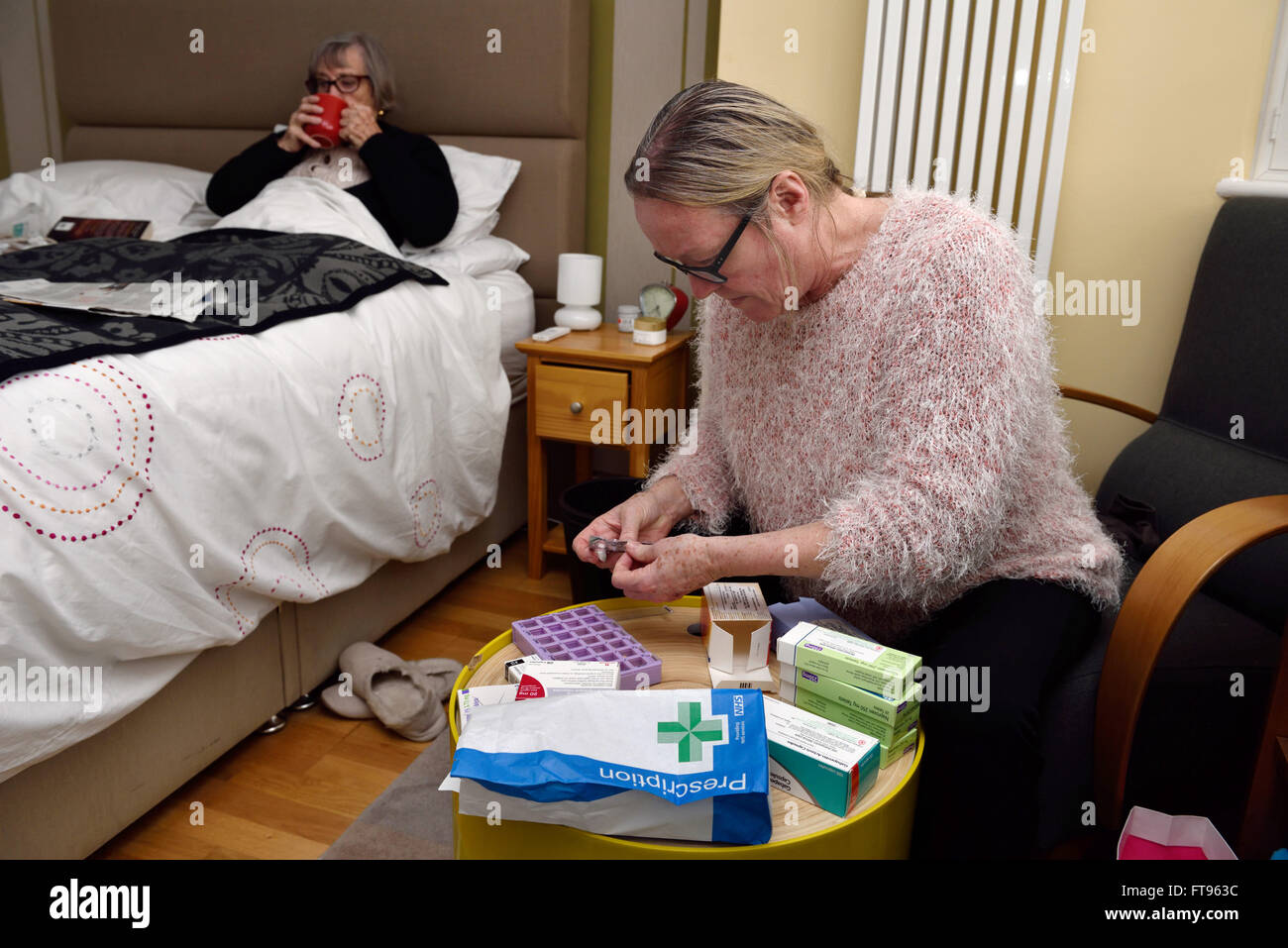 An elderly woman sitting in her bed being cared for in her home by her daughter who is checking her many boxes of - Stock Image