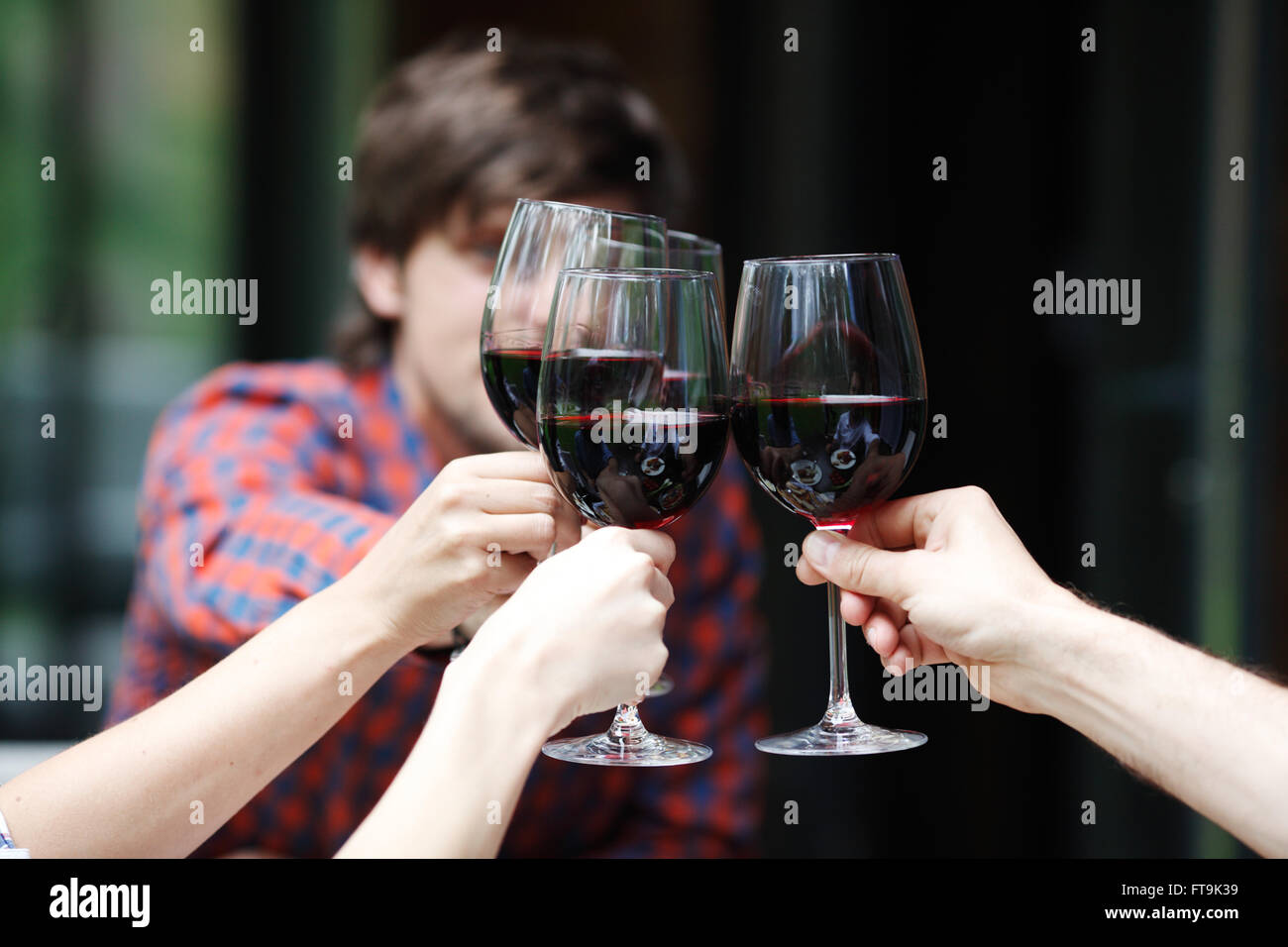 Friends clink glasses of red wine at outdoor dinner - Stock Image
