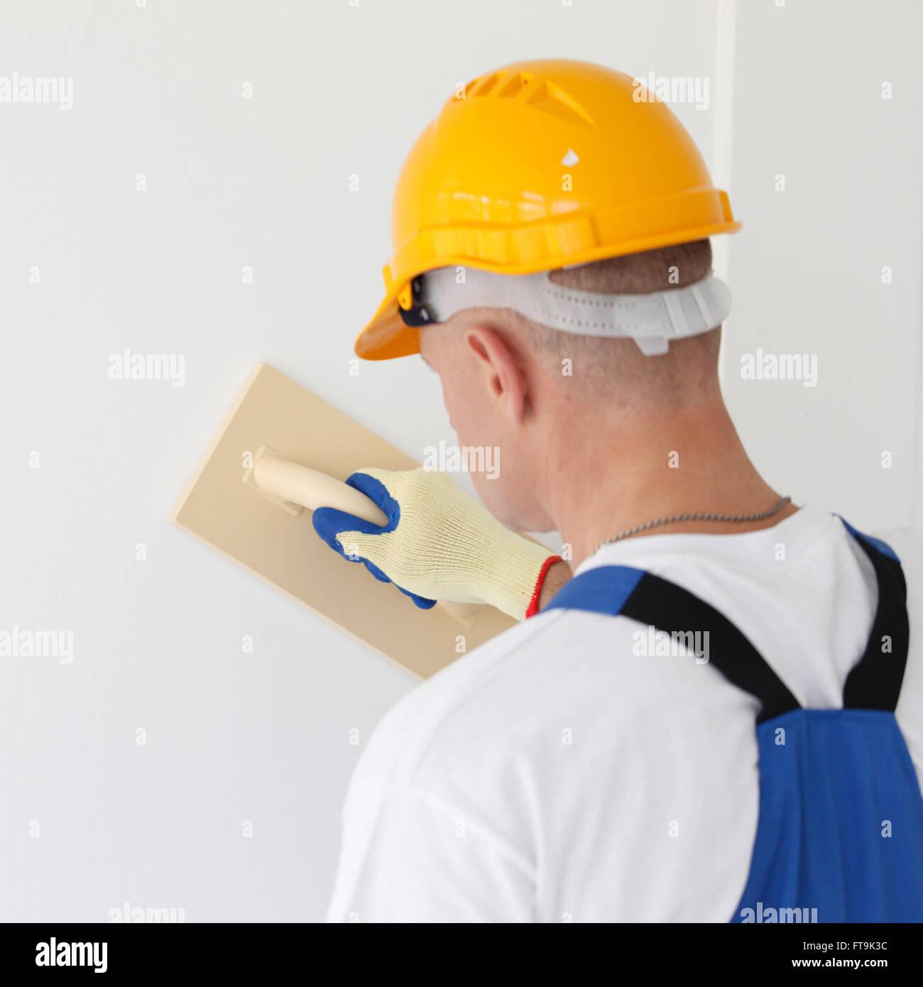 Male plasterer in uniform polishing the wall - Stock Image