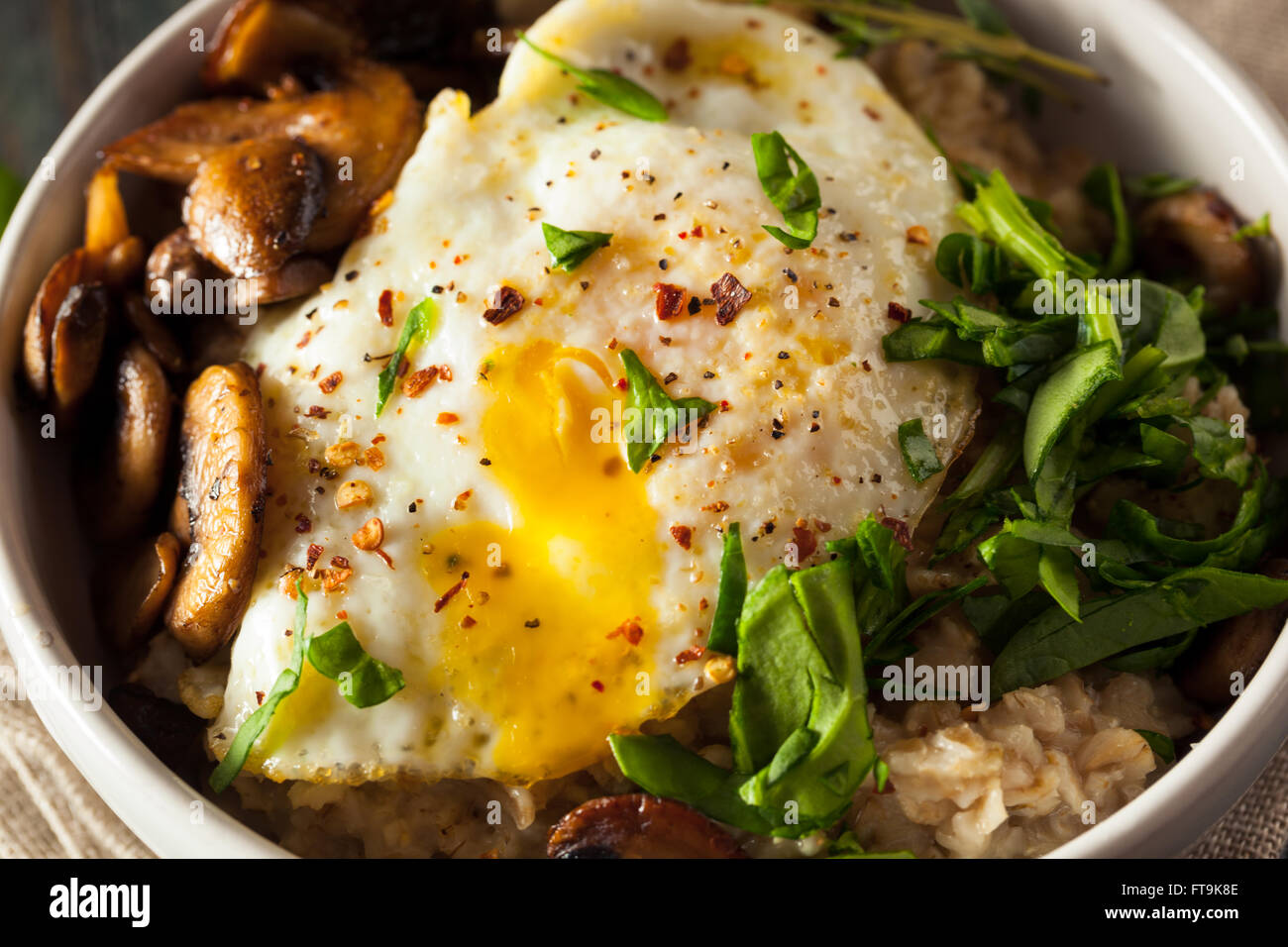 Healthy Homemade Savory Oatmeal with Eggs Mushrooms and Spinach - Stock Image