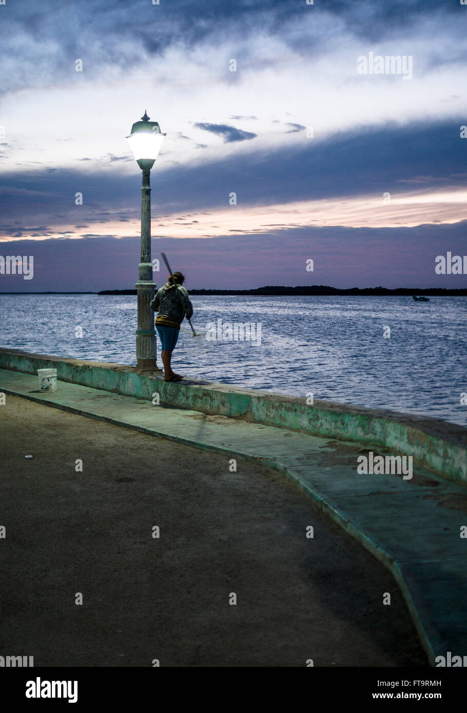Scooping Shrimp at dusk on Sea Wall at Rio Lagartos. A street lamp glows with a sunset sky as a shrimp fisher rotates - Stock Image