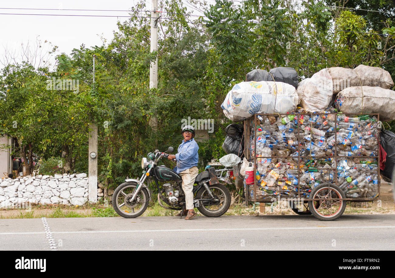 Overloaded Plastic Recycler. A small motorcycle towing a huge trailer overloaded with plastic bottles along the - Stock Image