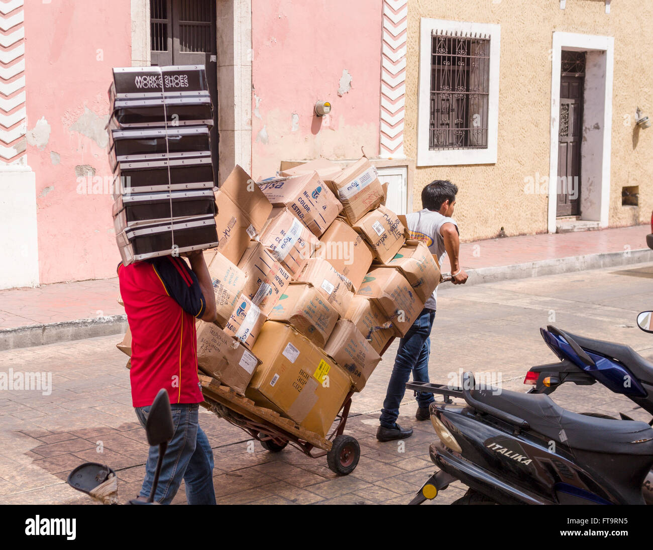 Shop Deliveries. Two men, one with a pull cart and one with shoe boxes piled high walk the cobbled street to deliver - Stock Image