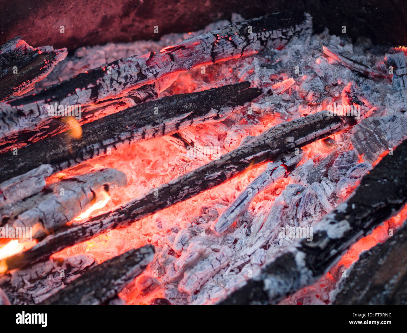 Glowing Embers in a hot wood fire. Ash covered wood glows red in this burned down fire. - Stock Image
