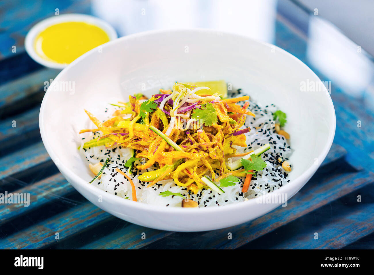 curry sauce vegetable salad with noodles and sesame modern asian fusion dish - Stock Image