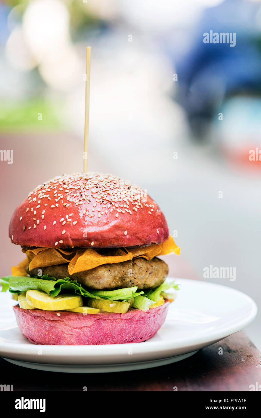 chicken burger with gherkins and crisps in beetroot bread bun - Stock Image