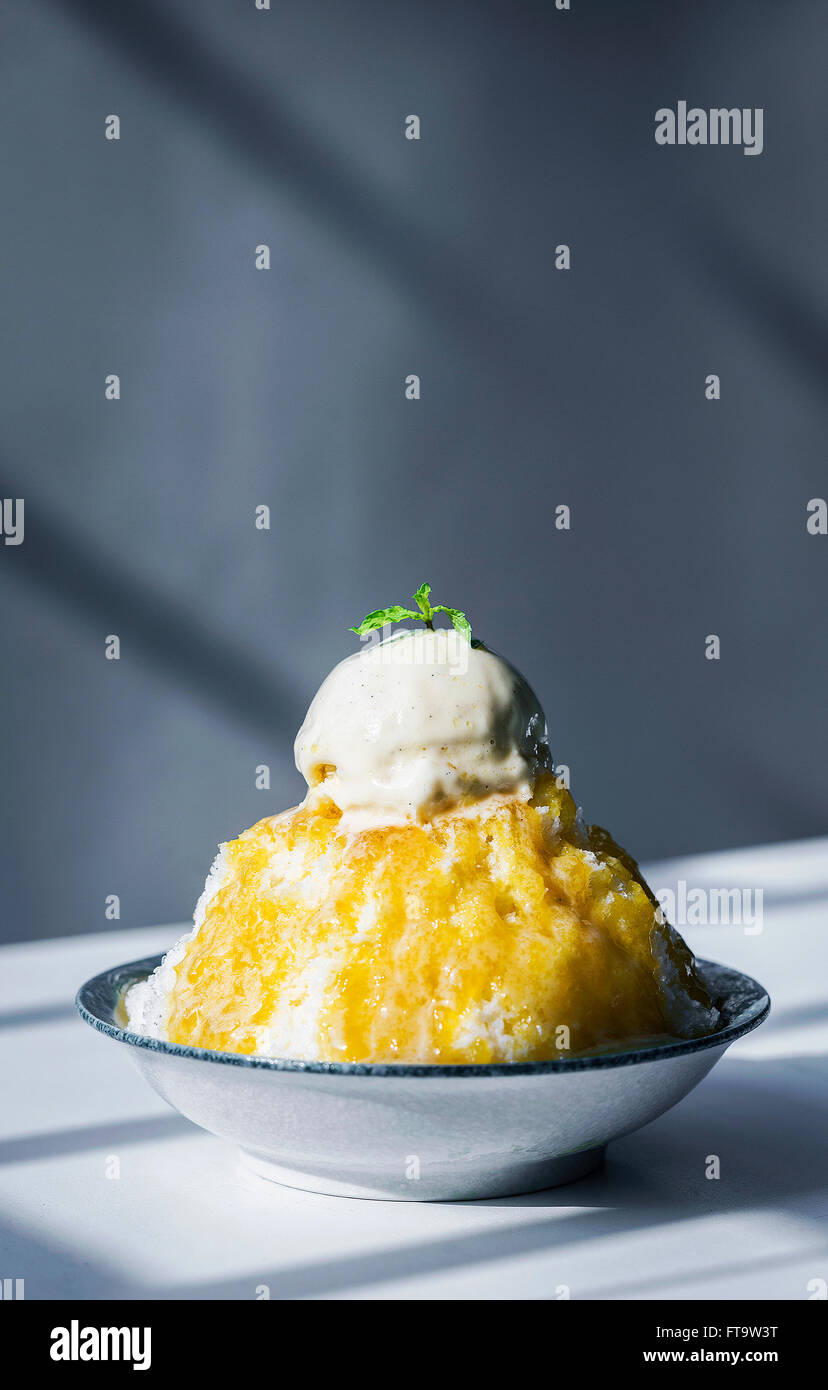 coconut sorbet with mango coulis sauce and vanilla ice cream - Stock Image