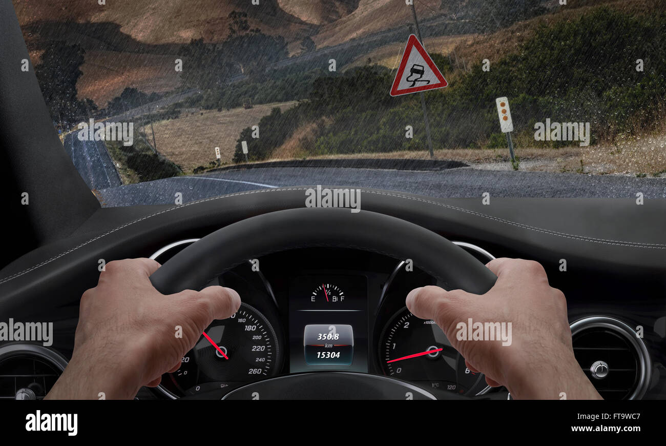 Car slipping on a road in the rain. Alongside the road is a sign for slippery road. Rain splashed windshield. - Stock Image