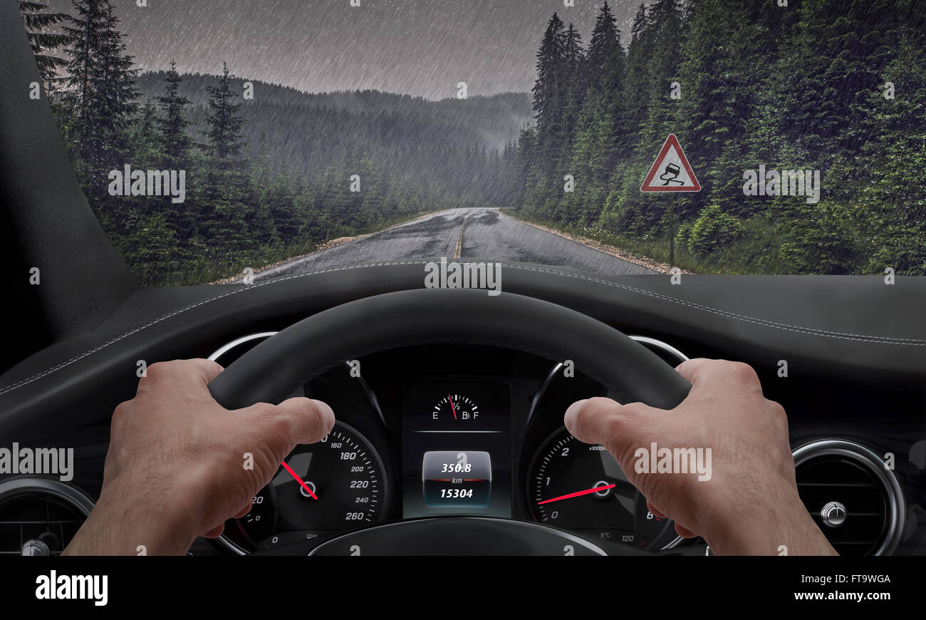 Driving in rainy weather. View from the driver angle while hands on the wheel. Alongside the road is a sign for - Stock Image