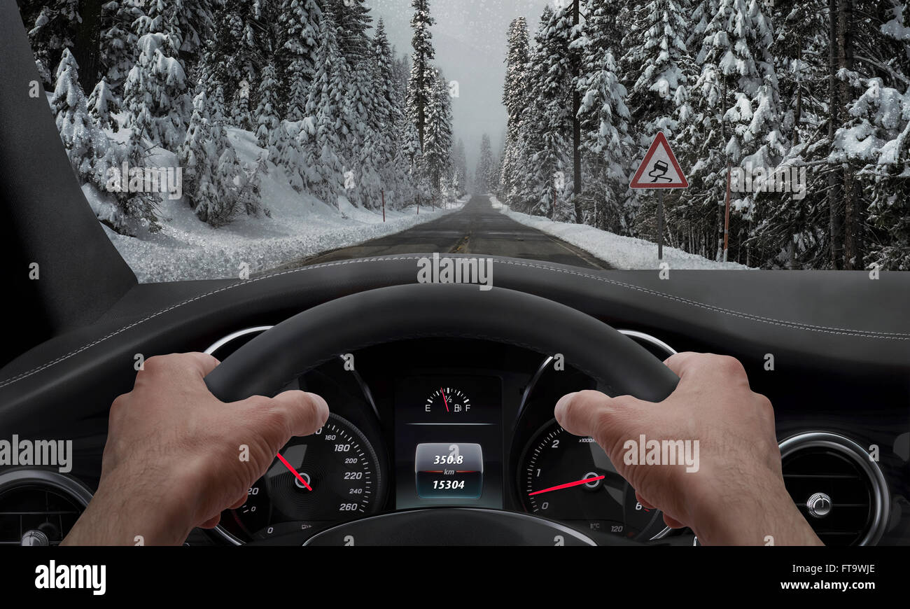 Driving in snowy weather. View from the driver angle while hands on the wheel. Alongside the road is a sign for - Stock Image