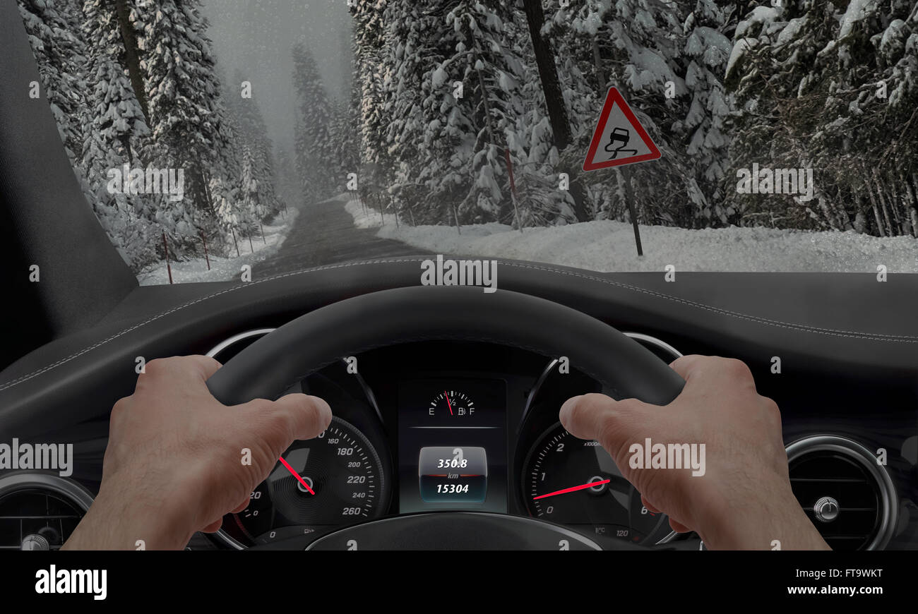 Car slipping on a road in the snow ice. Alongside the road is a sign for slippery road. Stock Photo