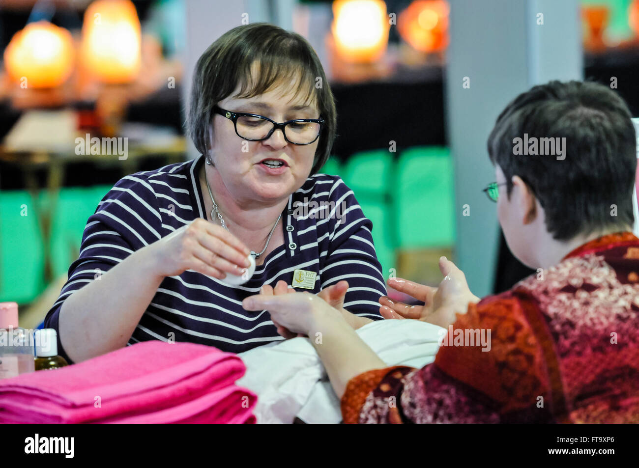 An aromatherapist applies oils to the hands of a patient at a holistic and spiritual fair - Stock Image