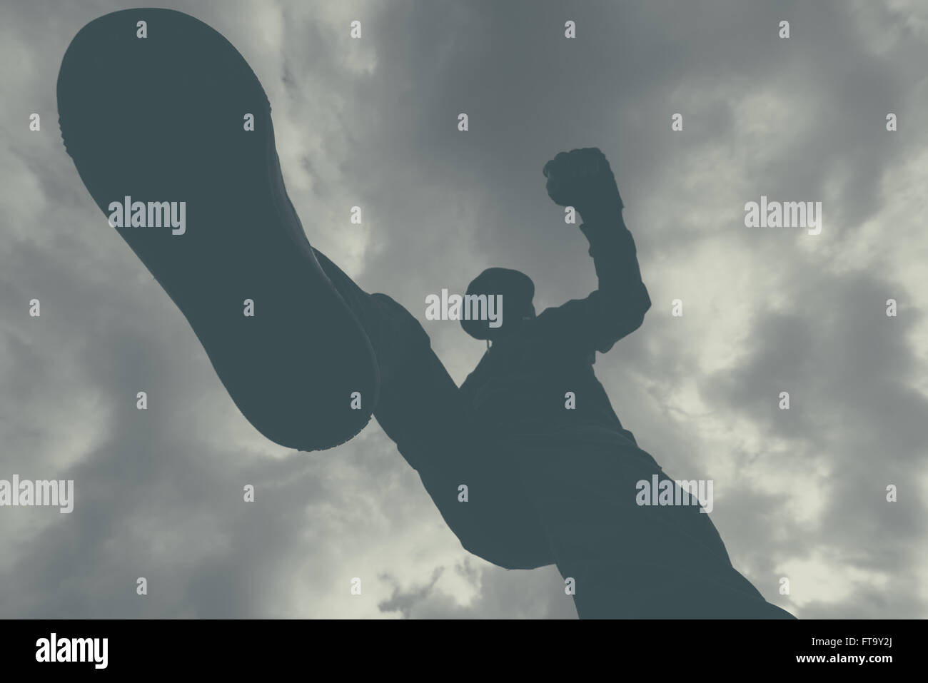 Violent attack, unrecognizable hooded male criminal kicking and punching victim on the street. monochromatic image. - Stock Image