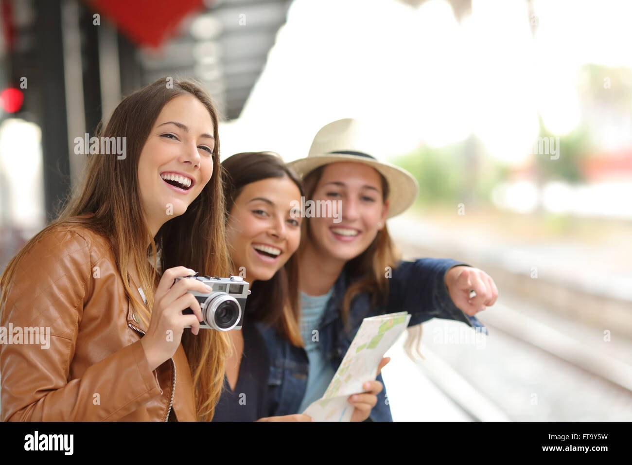 Group of three traveler girls traveling and waiting in a train station platform - Stock Image