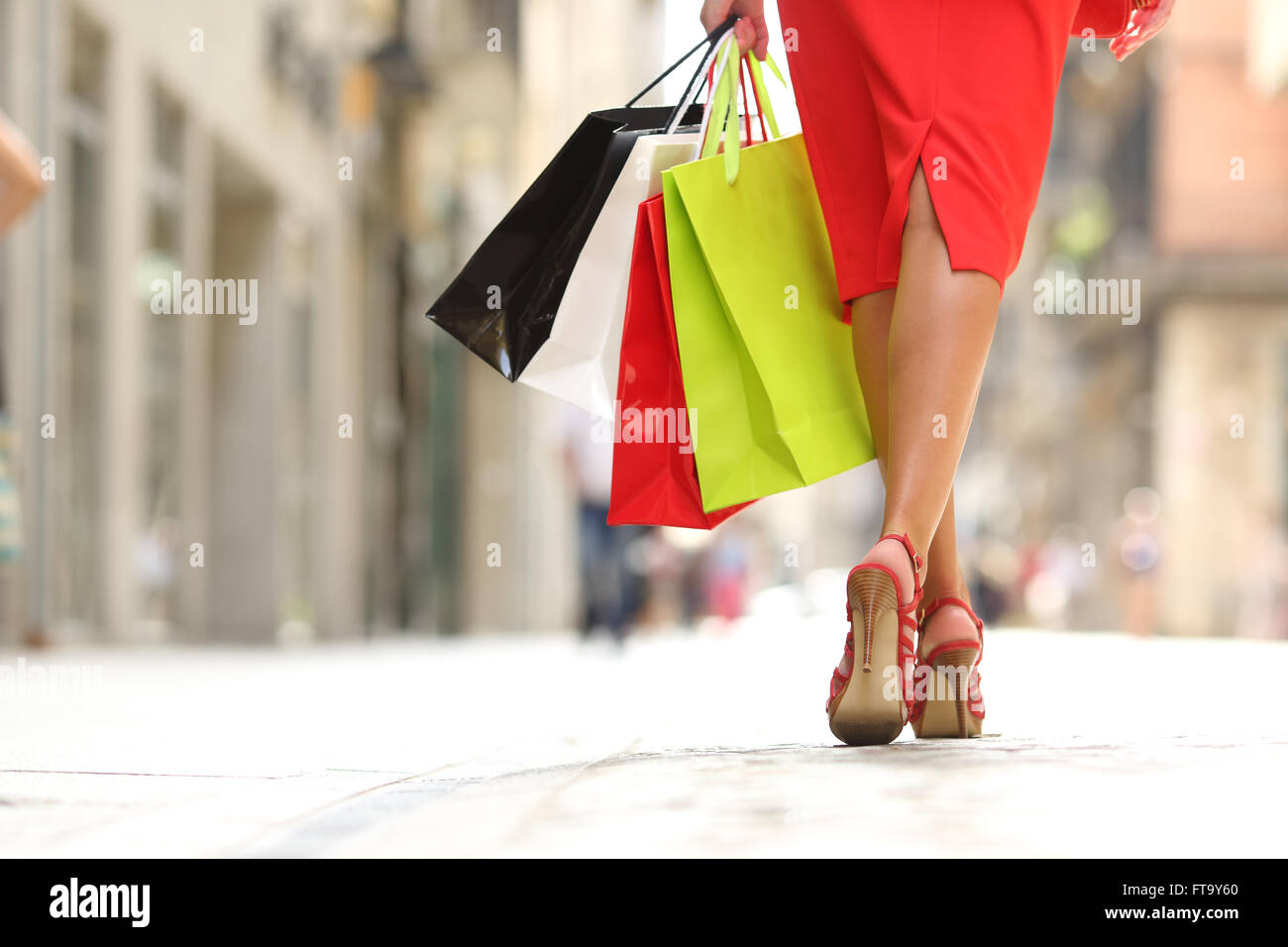 Back view of a fashion shopper woman legs walking with colorful shopping bags in the street - Stock Image