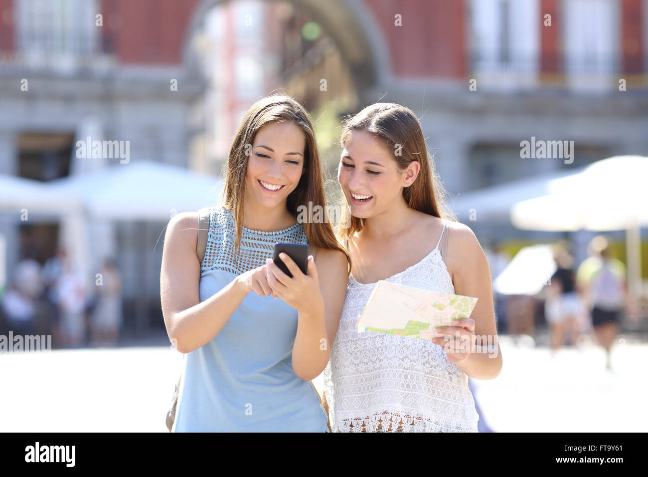 Two tourist friends consulting an online guide on a smart phone in the street - Stock Image