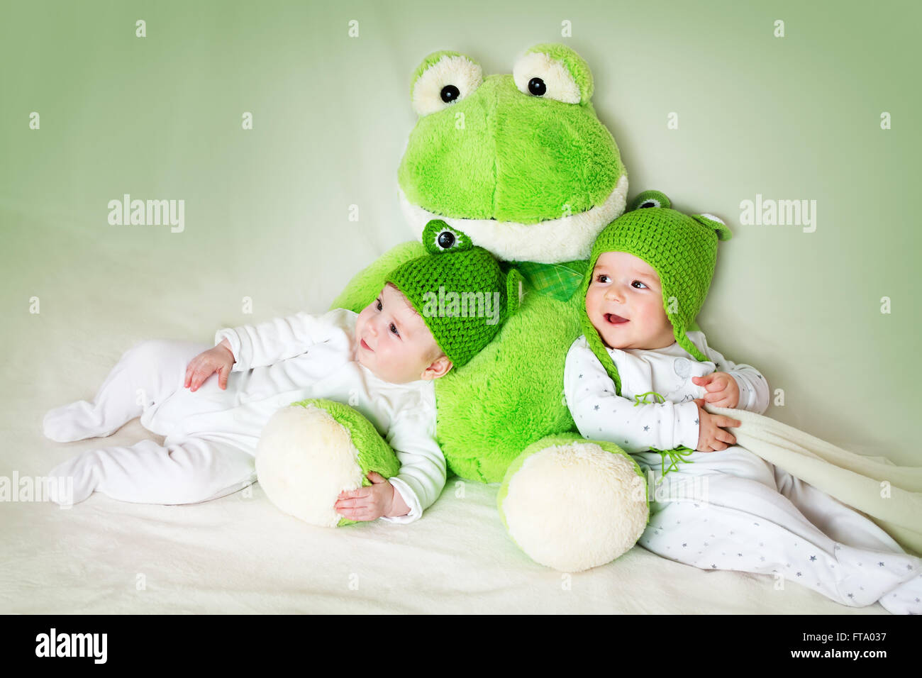 two cute babies lying in frog hats with a soft toy - Stock Image