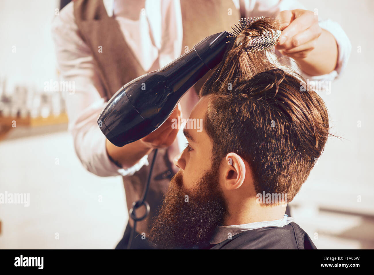 Professional barber drying hair of his client - Stock Image