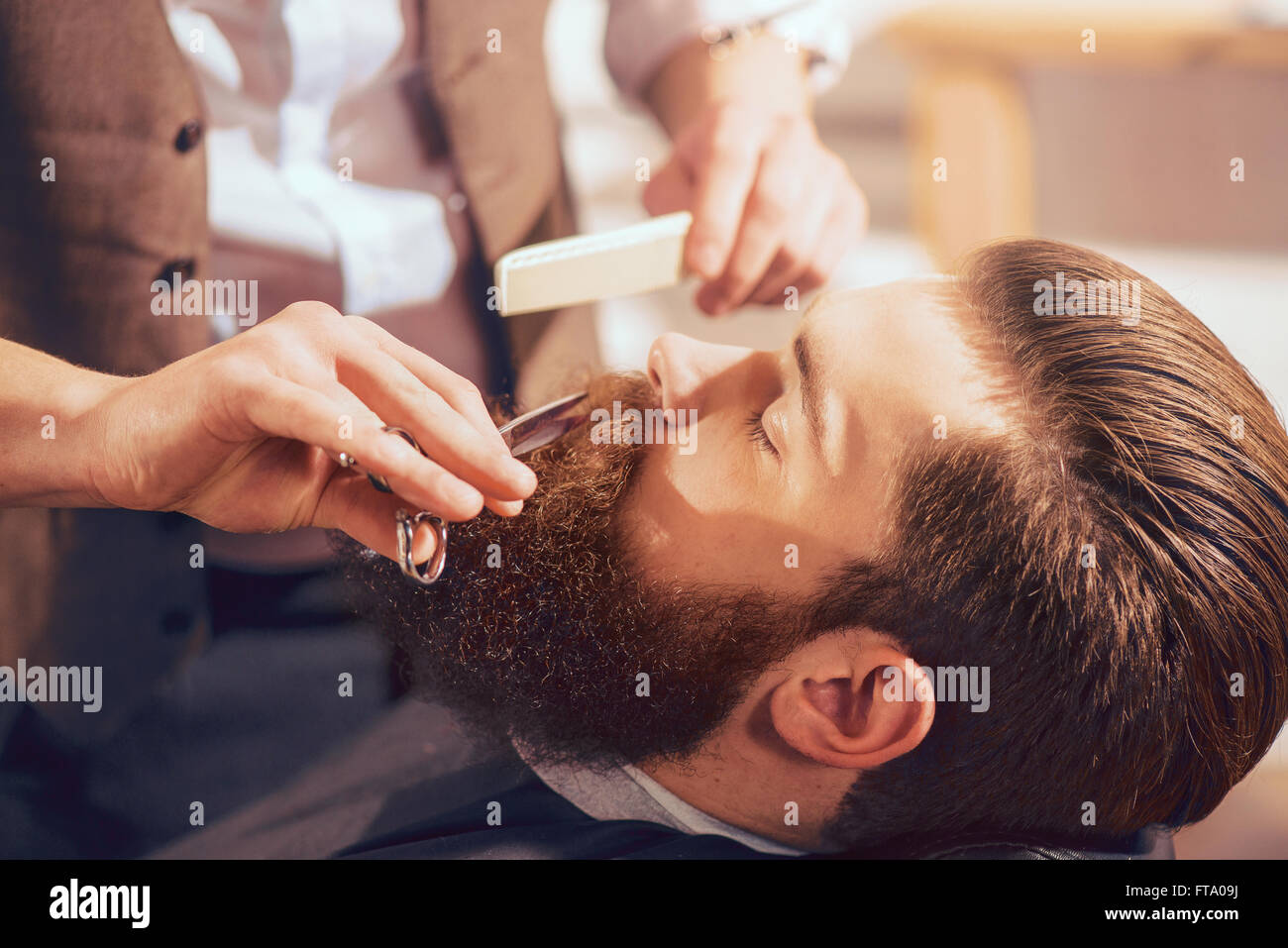 Professional barber cutting beard of handsome man - Stock Image