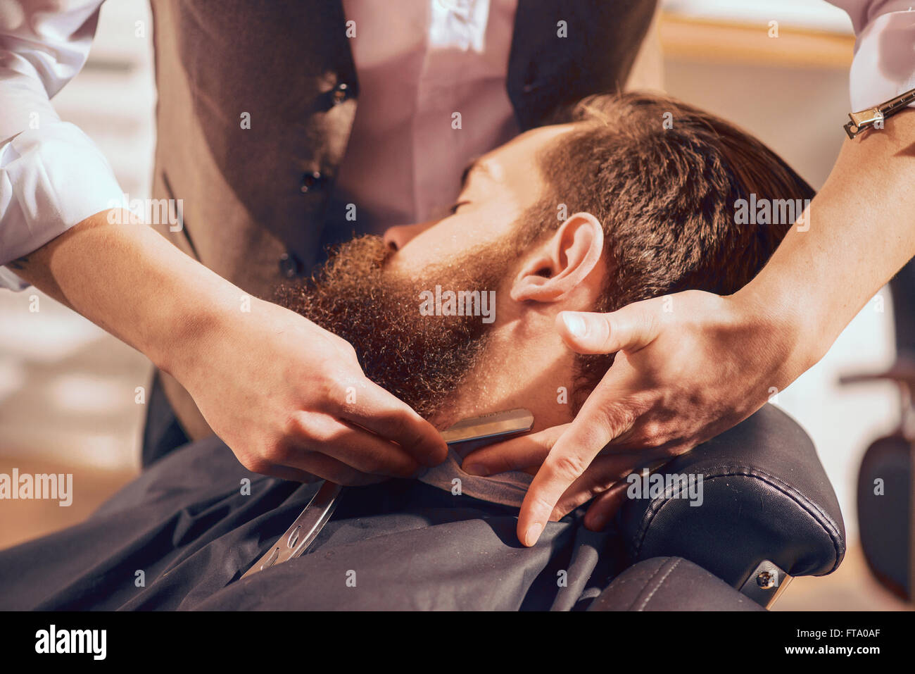 Professional barber shaving beard of his client - Stock Image