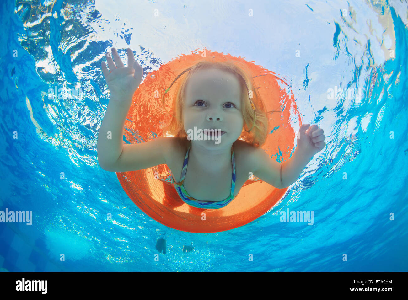 Funny underwater photo of baby girl swimming with fun on orange tube and diving in clear aqua park pool. Stock Photo