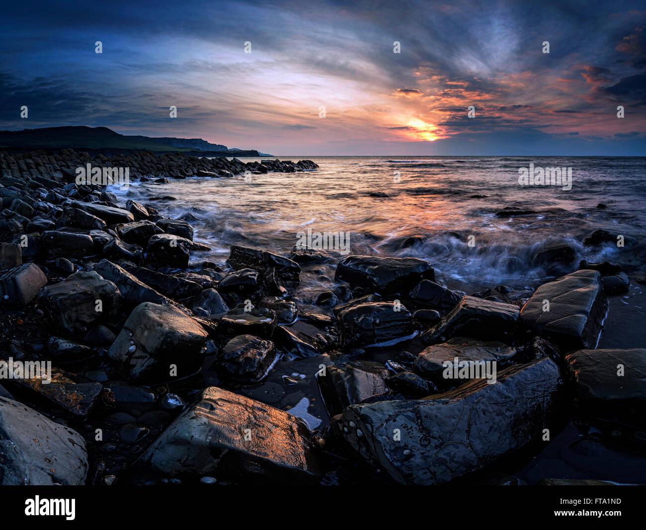 Stunning sunset landscape image of rocky coastline in Dorset England - Stock Image