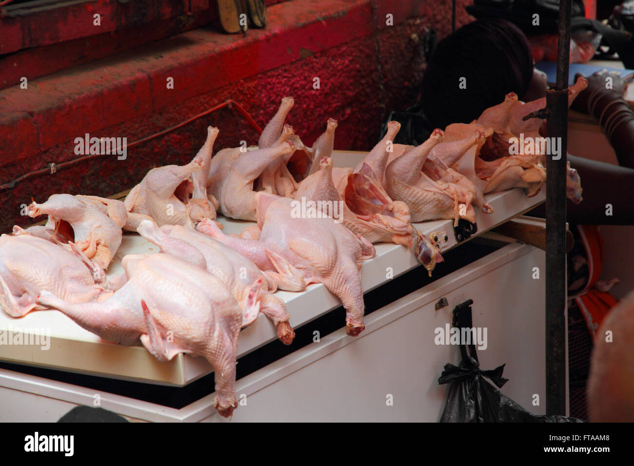 Chicken carcasses for sale in an open air african market and display on top of a freezer lid. - Stock Image