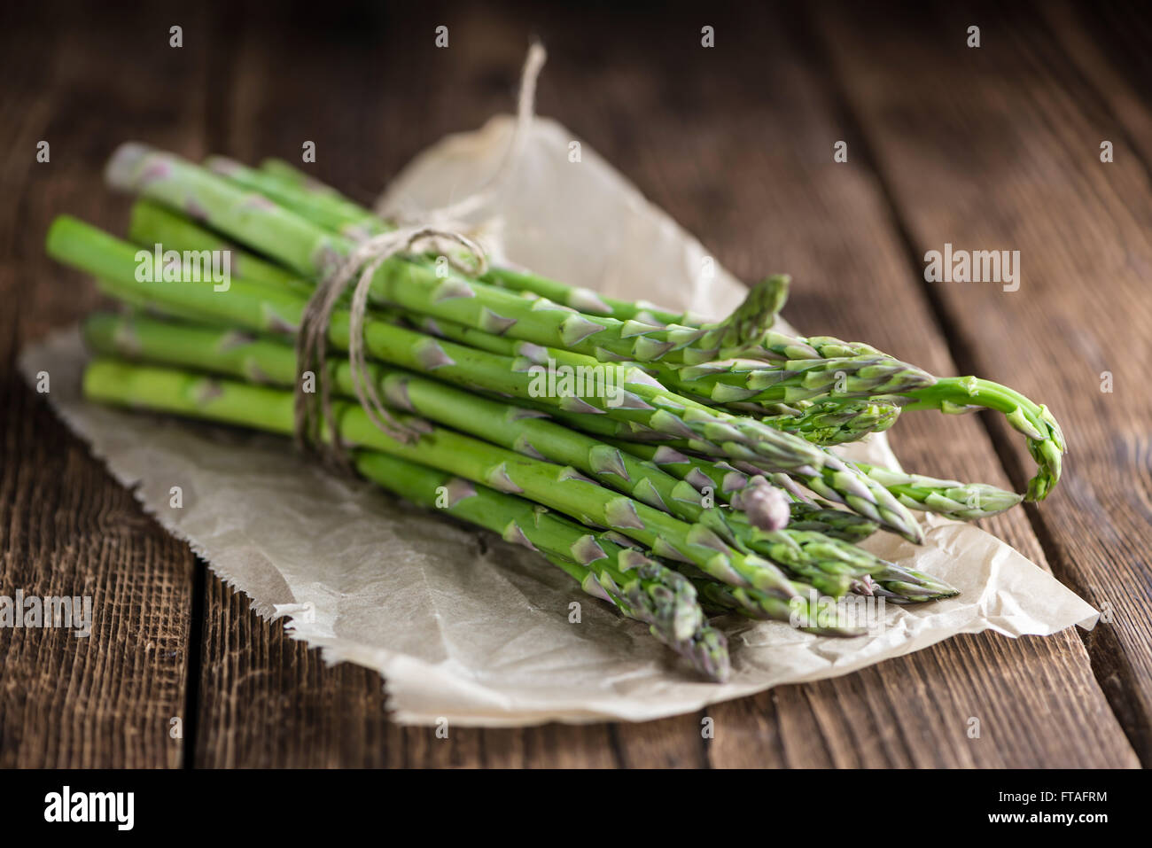 Green Asparagus (fresh harvested) on an old wooden table (selective focus) - Stock Image