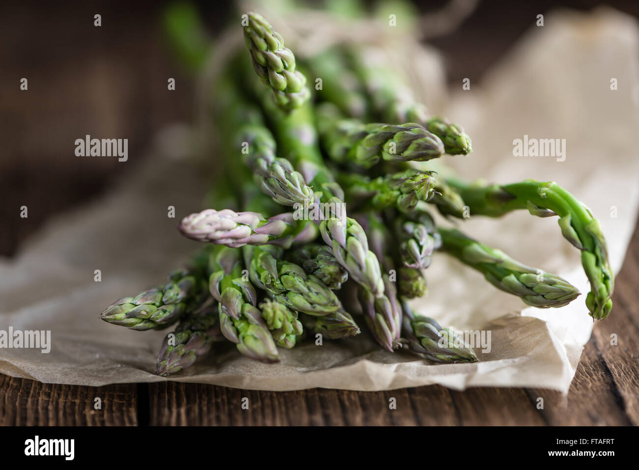 Portion of green Asparagus (close-up shot) on wooden background - Stock Image