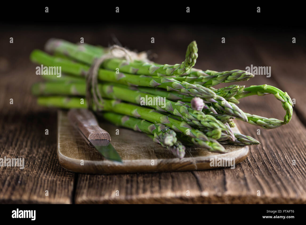 Fresh green Asparagus (selective focus, close-up shot) on wooden background - Stock Image