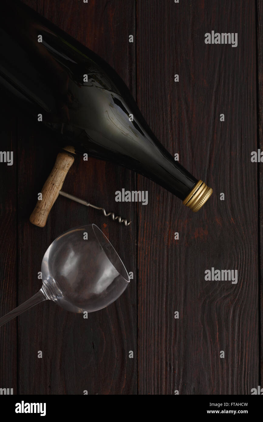 Bottle of red wine next to to empty glass with corkscrew on wooden table. Flat lay, above view, copy space,Chiaroscuro - Stock Image