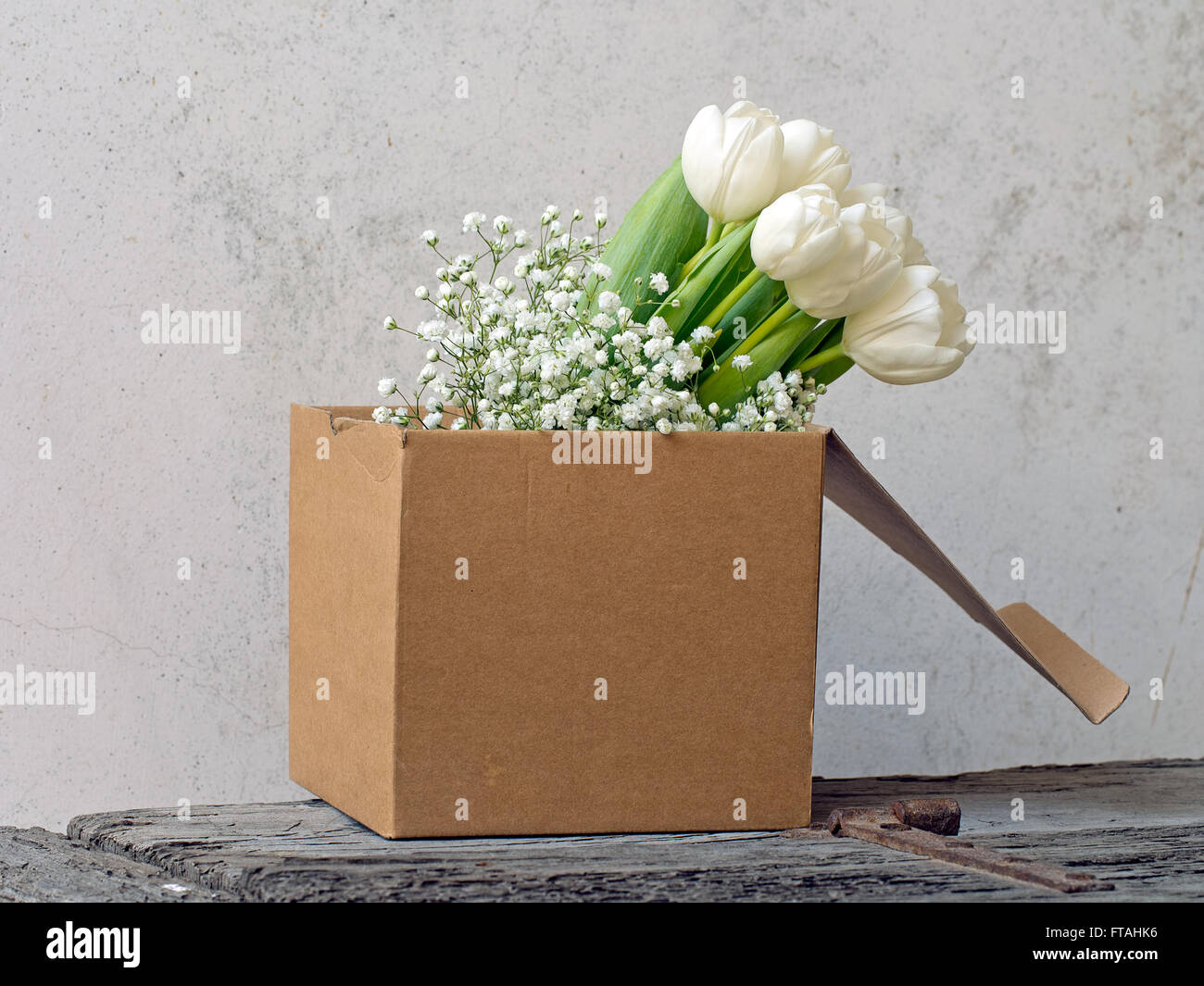 Beautiful spring flowers. Shabby chic in cardboard box on rustic dresser. - Stock Image