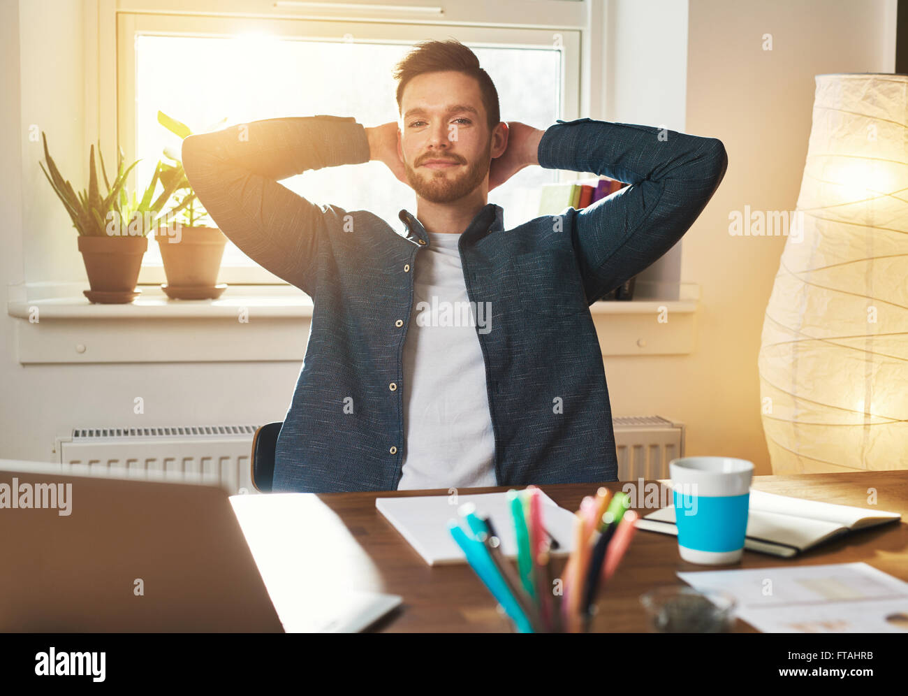 Relaxed Entrepreneur sitting with his hands raised behind his neck looking at the camera with a serious speculative - Stock Image