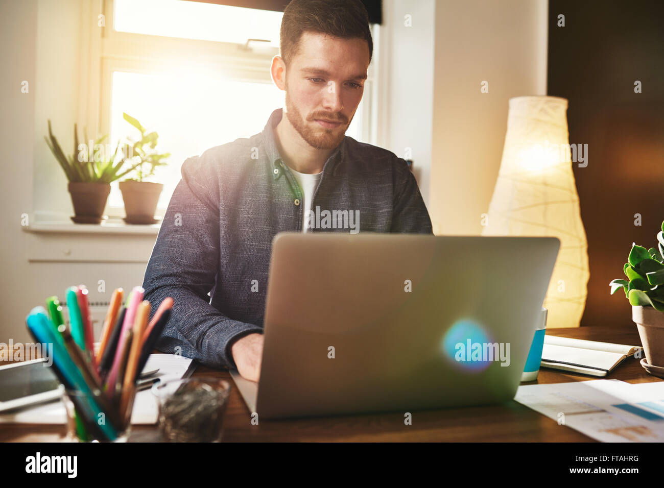 Worried businessman reading data on his laptop with a solemn expression as he works in his home office, colorful - Stock Image