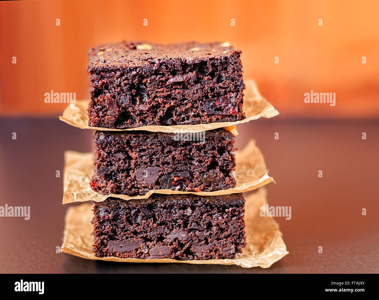 Three stacked chocolate chip brownies on parchment paper. - Stock Image