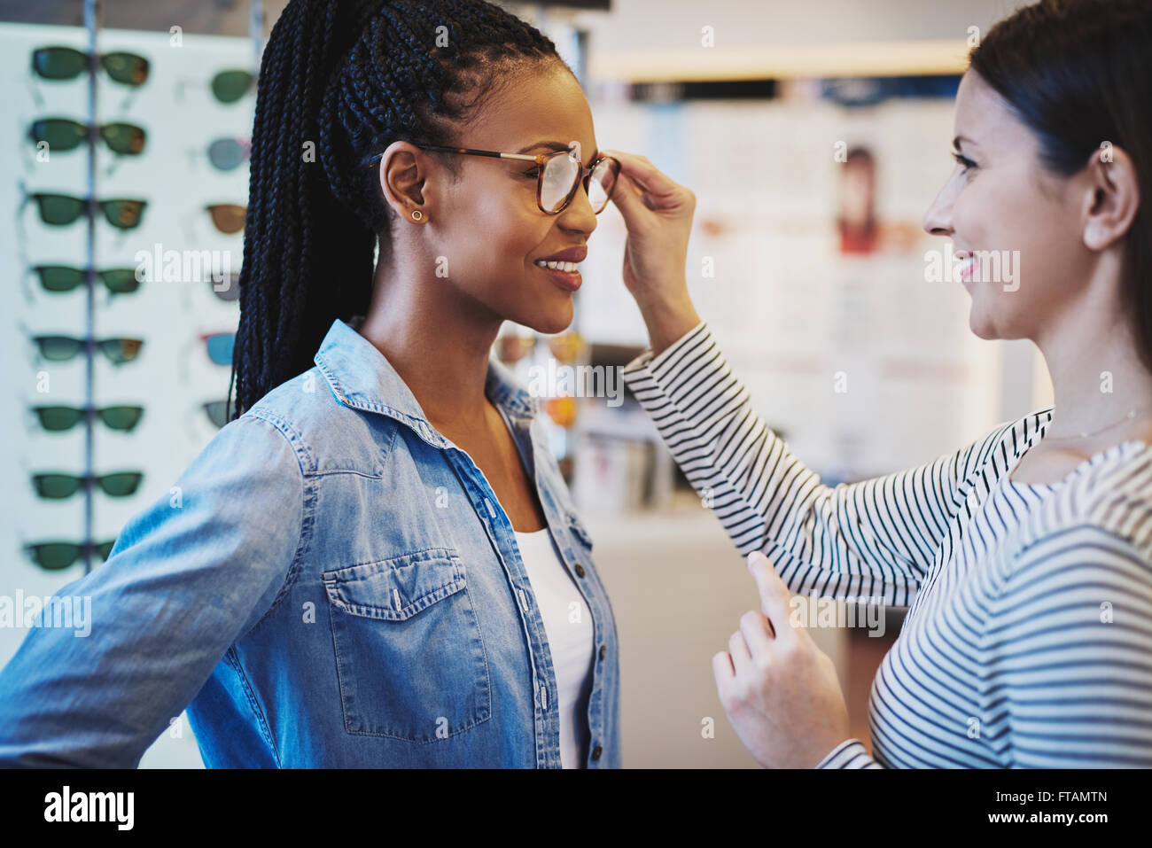 Optometrist helping a pretty African client to try on and purchase frames for a pair of eyeglasses - Stock Image