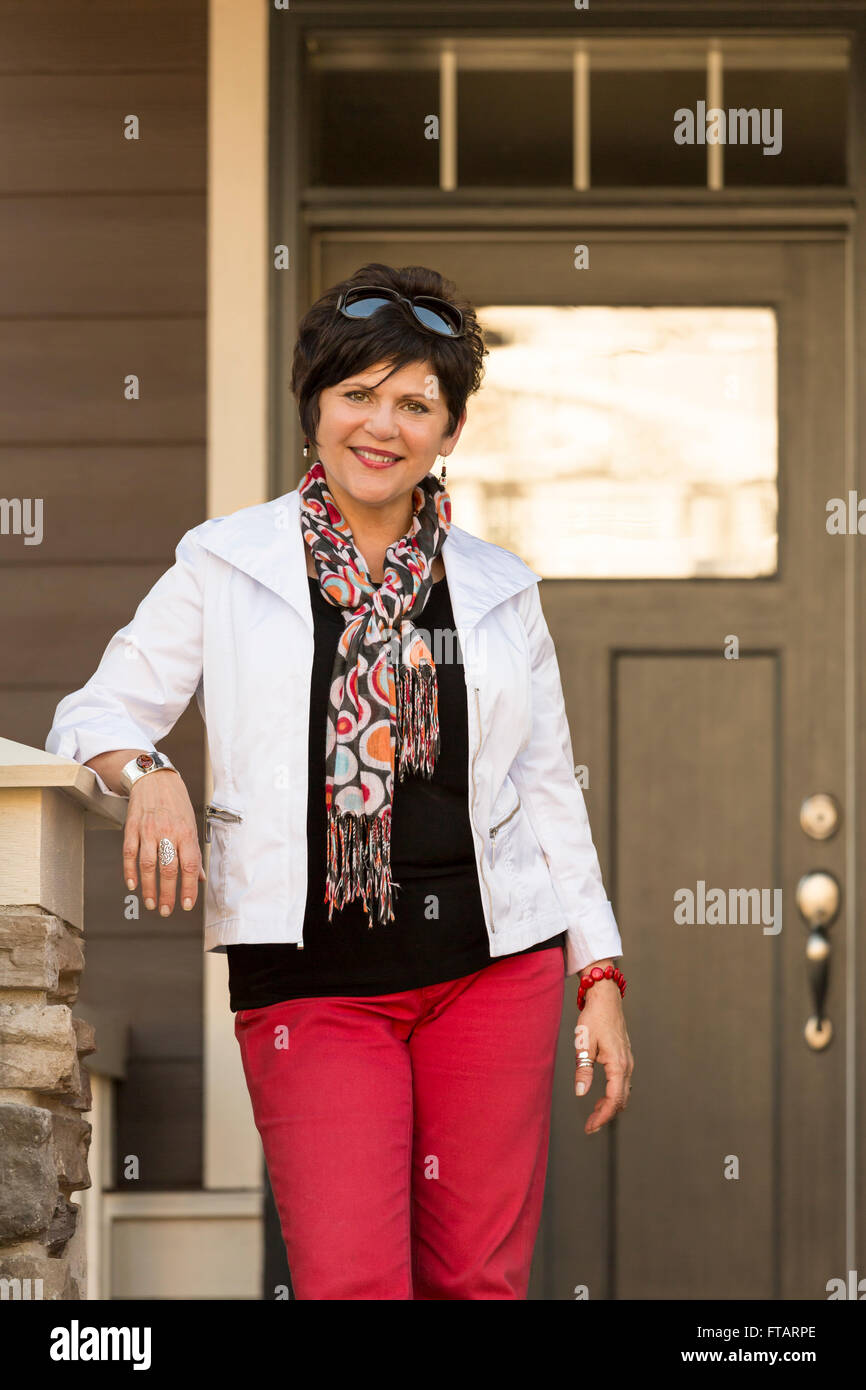 Happy, confident, mature, middle-aged woman standing in front of a house. She could be the home owner or a real - Stock Image
